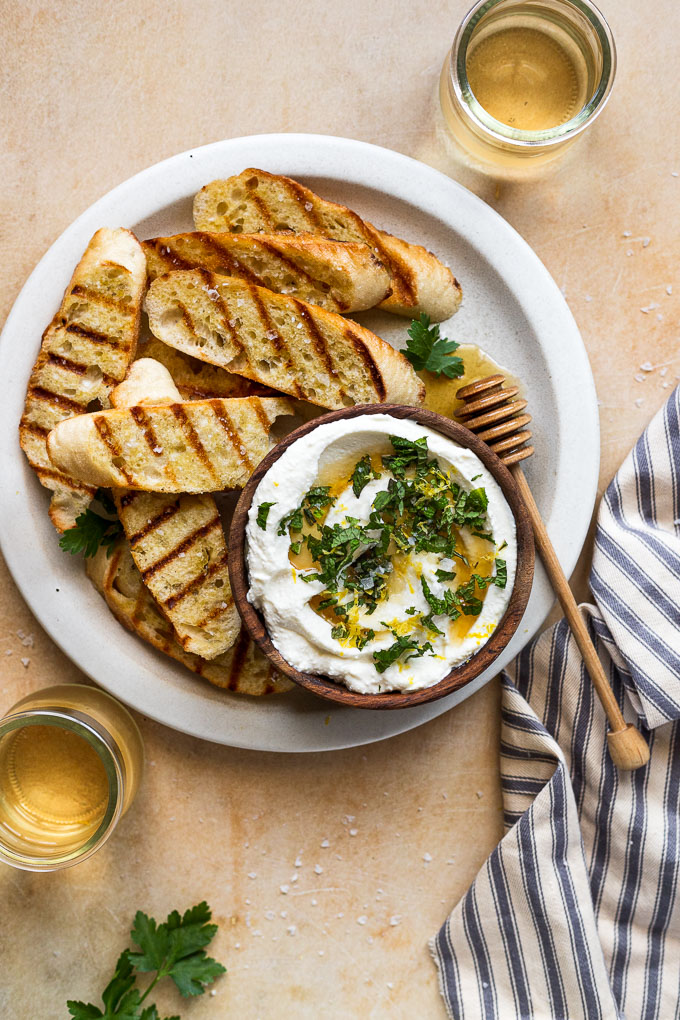 Bowl of whipped ricotta next to grilled baguette slices and whine glasses.