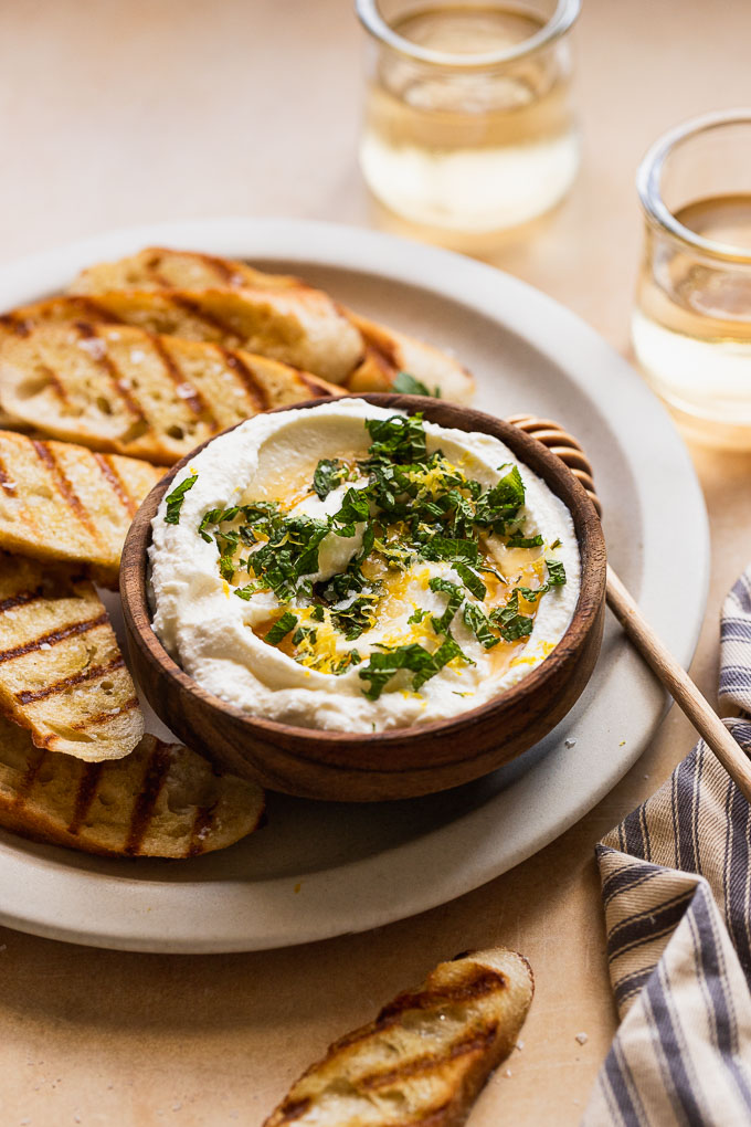 Side view of herb topping on whipped ricotta in a wood bowl next to wine glasses and bread.