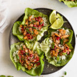 Plate of three lettuce wraps next to lime wedges and another plate.