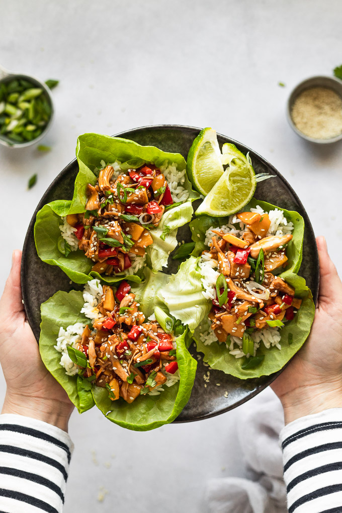 Hands holding plate of lettuce wraps.