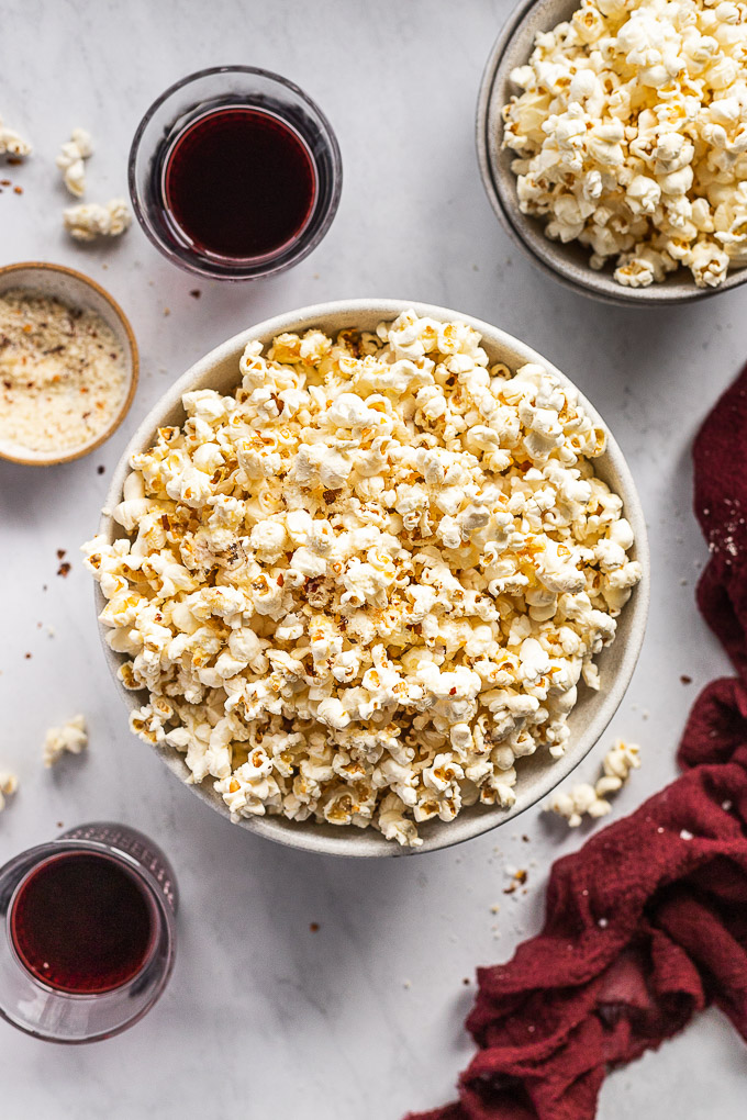 Large bowl of popcorn next to smaller one and two wine glasses.