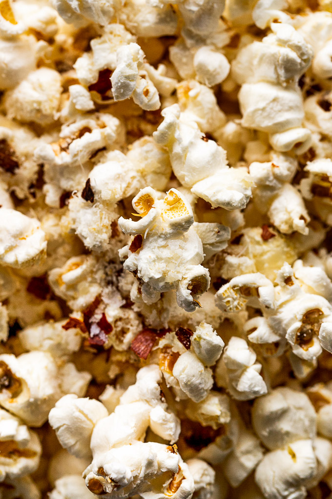Up close look at popcorn kernels with parmesan and red pepper flakes on top.
