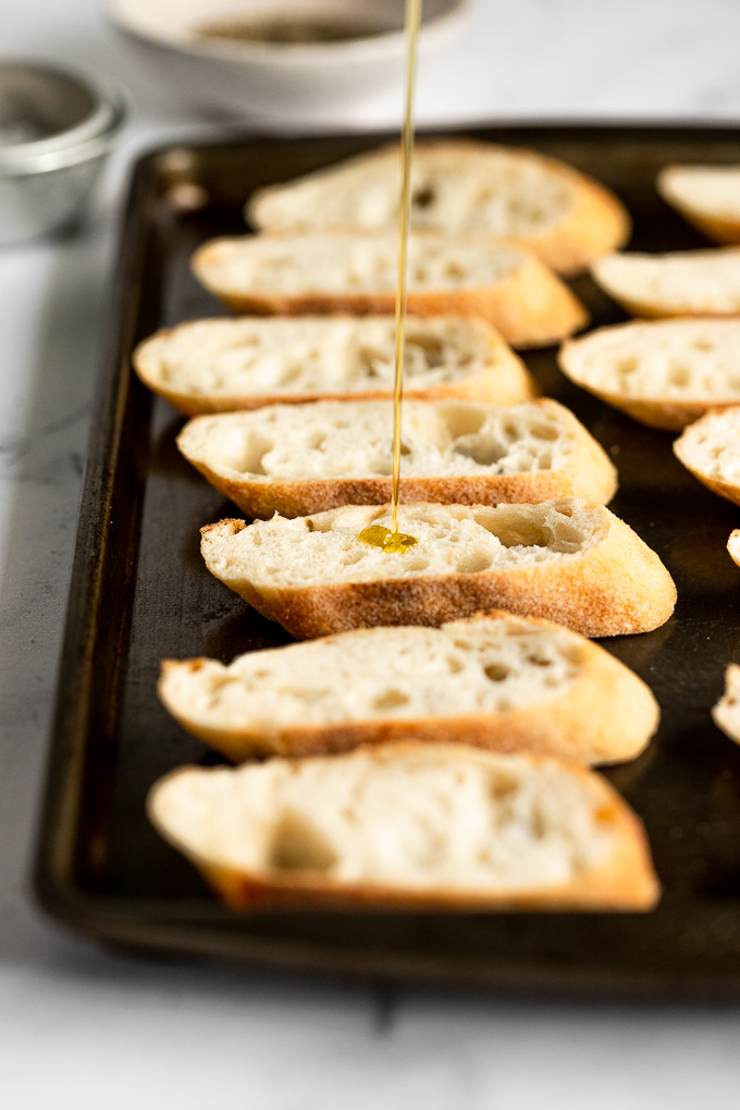 Drizzle of olive oil on sliced baguette.