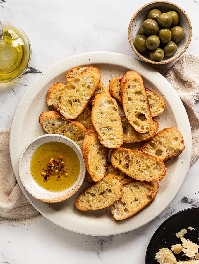 Plate of crostini with small bowl of olive oil next to a bowl of olives and parmesan cheese.