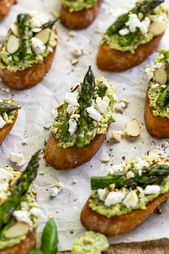 Crostini on parchment paper with asparagus and goat cheese.