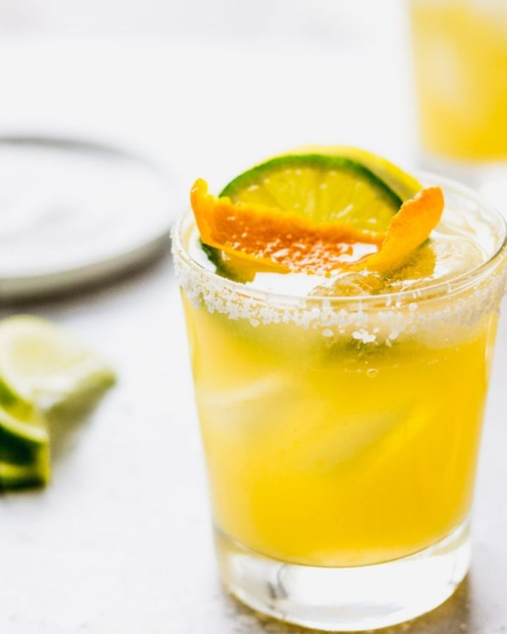 Triple citrus margarita with lime and orange garnish.