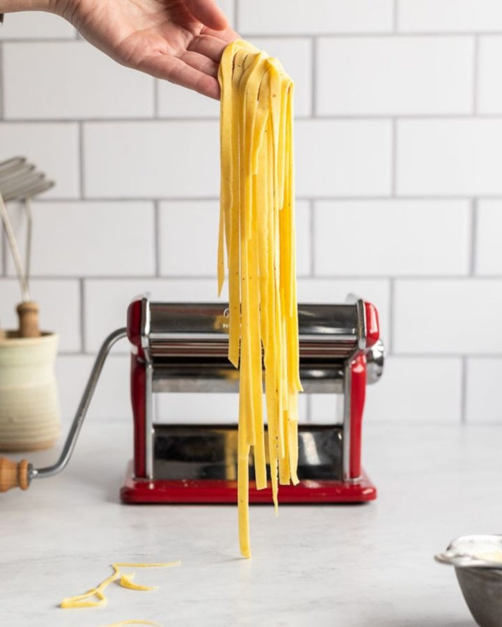 Hand holding string of fettuccine noodles in front of pasta machine.