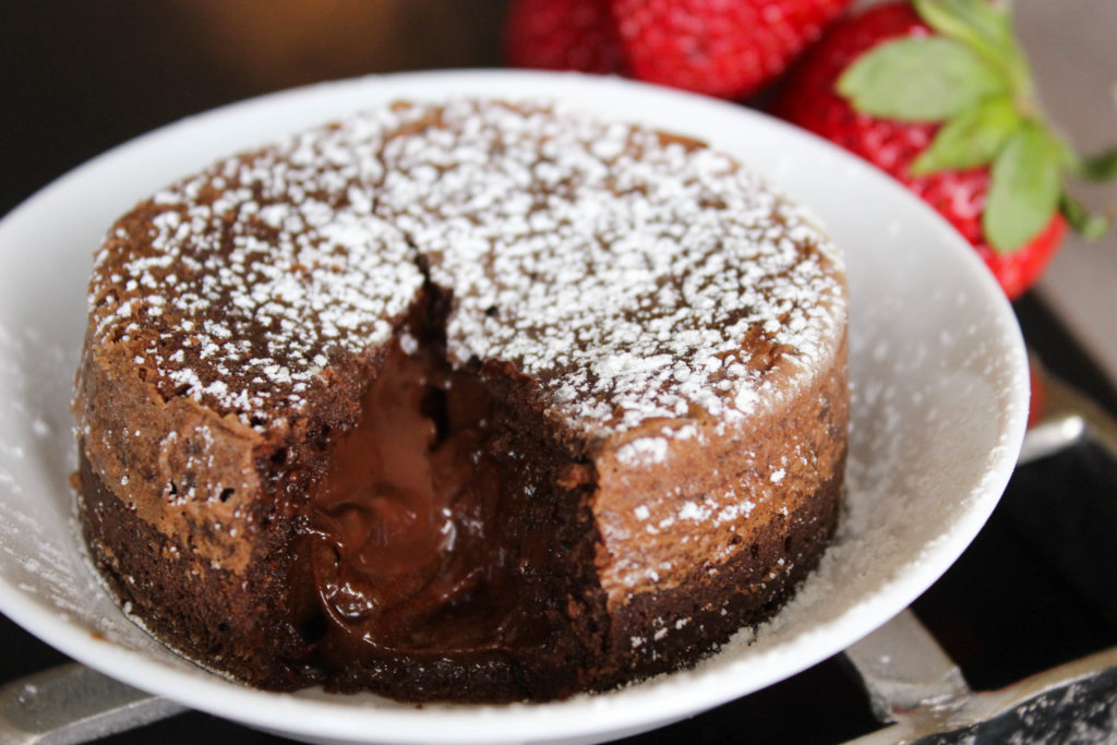 Molten chocolate cake cut open with melted chocolate and powdered sugar.