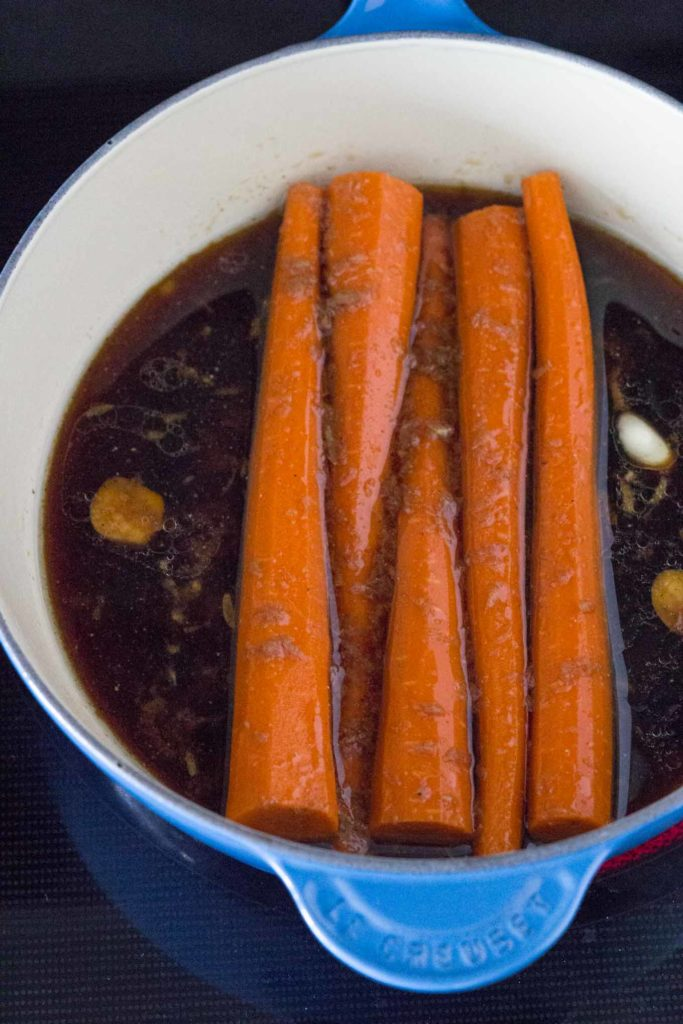 Dutch oven with sauce and carrots.