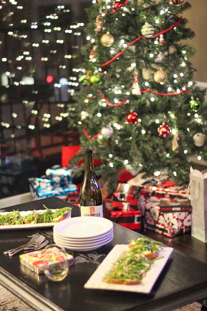 Table with appetizers in front of Christmas tree.