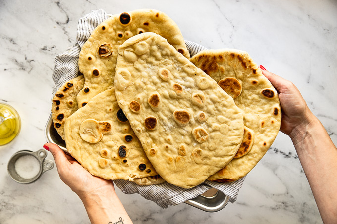 Hands holding baking tray of flatbreads.