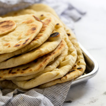 Flatbreads stacked on linen in baking tray.