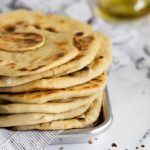 stacked flatbreads on metal tray with linen.