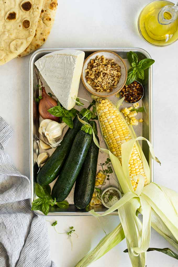 Tray with zucchini, corn, garlic, brie, walnuts, and basil.
