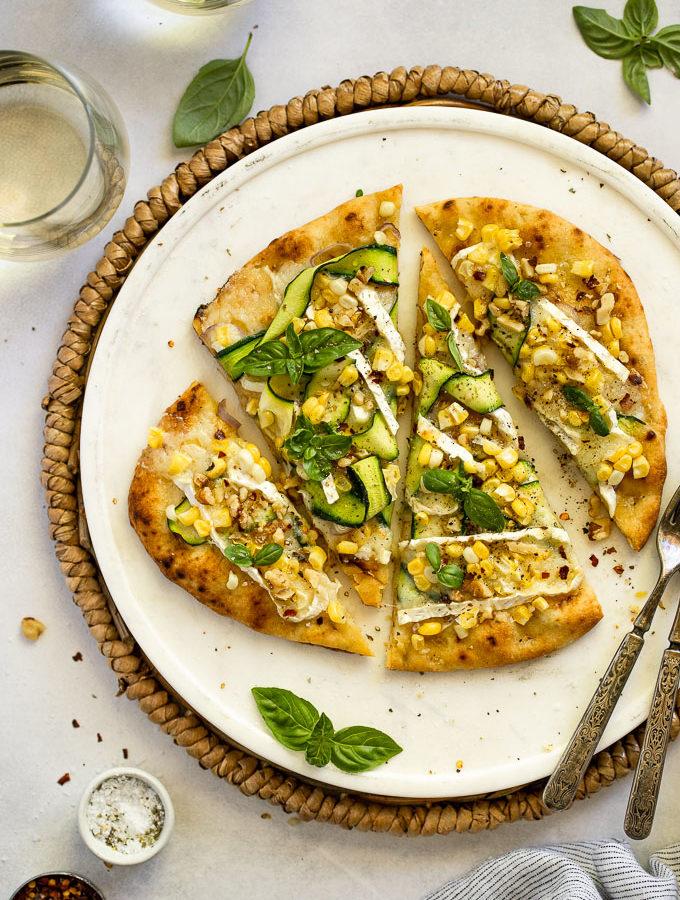 Zucchini flatbread on white tray next to wine glasses.