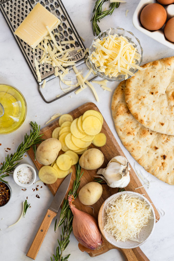 Cutting board with sliced potatoes, shallot, and garlic, next to naan flatbread, shredded cheese and olive oil.