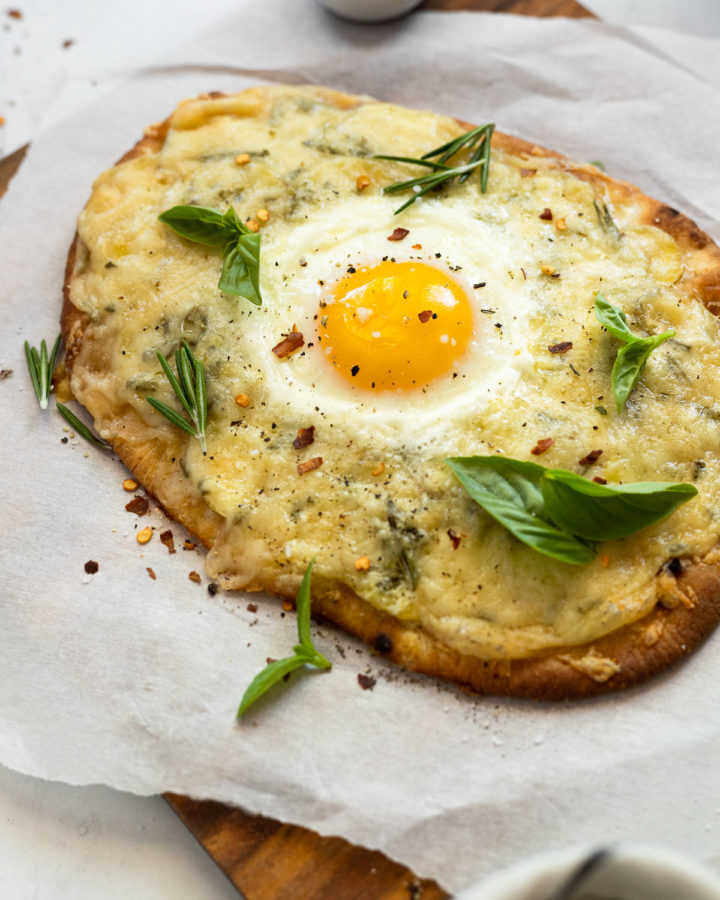 Naan flatbread on parchment paper topped with an egg and basil.