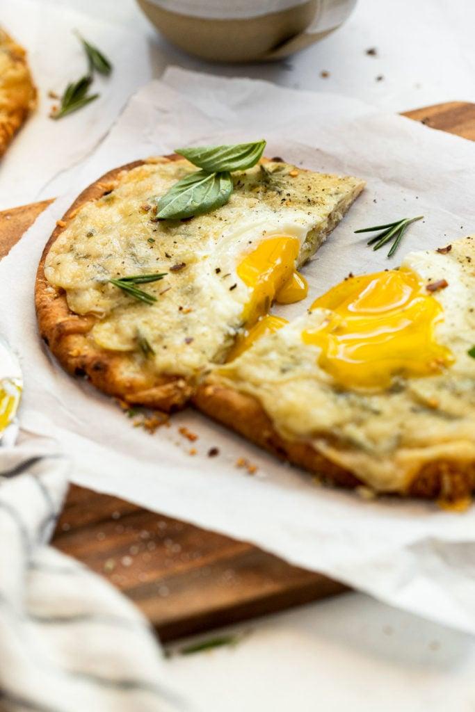 Flatbread cut in half with runny egg yolk.