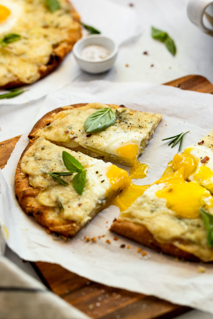 Slices of breakfast pizza with runny egg yolk.