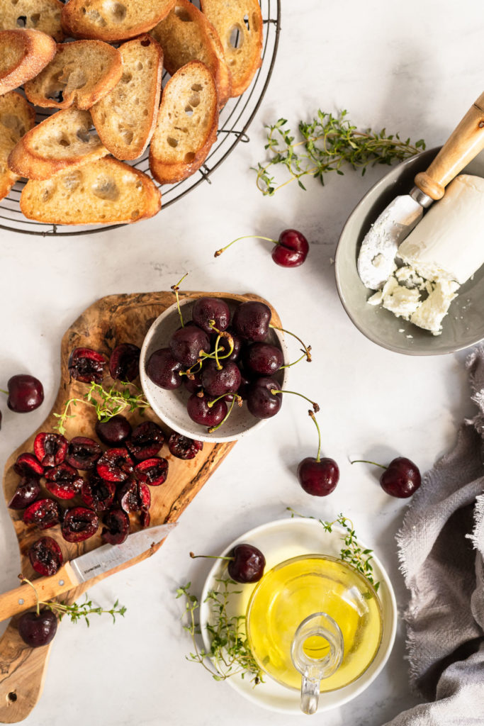 Cherries on cutting board next to goat cheese log, crostini, and olive oil.