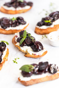 Roasted cherry crostini on parchment paper.