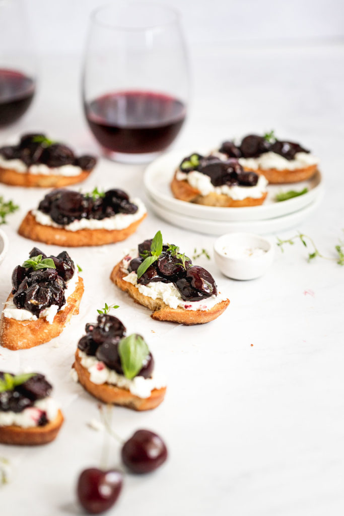 Crostini on parchment paper and plate next to wine glass.
