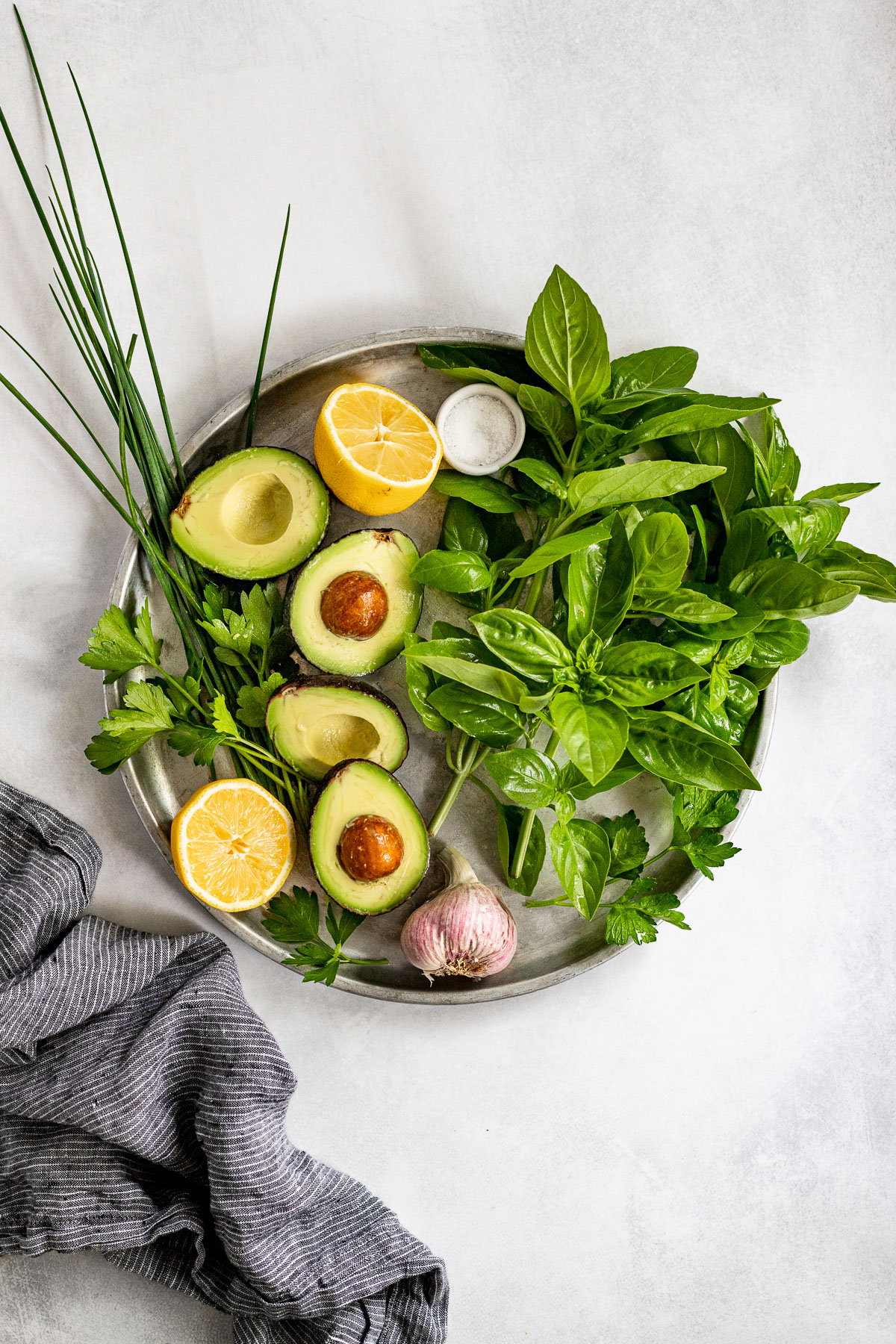 Tray with avocados sliced open, basil, parsley, chives, and lemon.