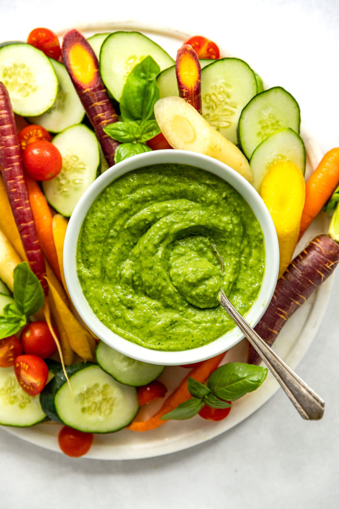 Avocado sauce in bowl on vegetable tray.