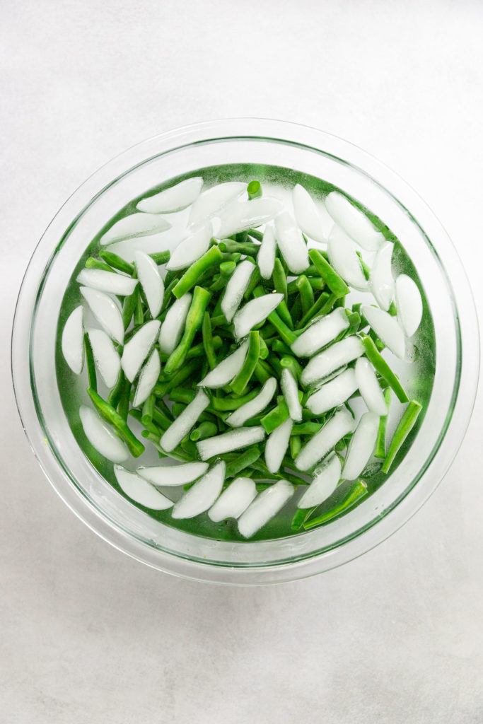 Glass bowl of ice water with green beans.