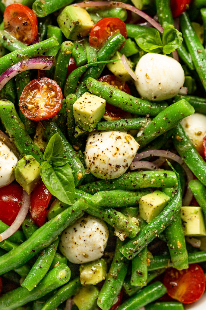 Up close look of green bean salad with mozzarella, black pepper, tomatoes, green beans, and basil.