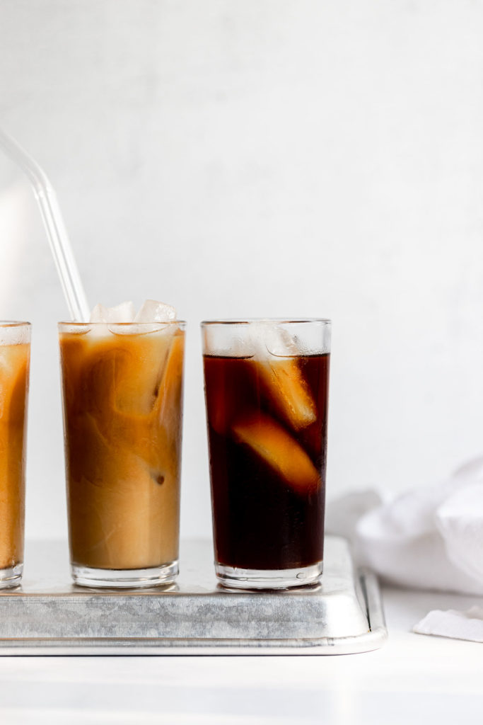 Three glasses of cold brew on metal tray.