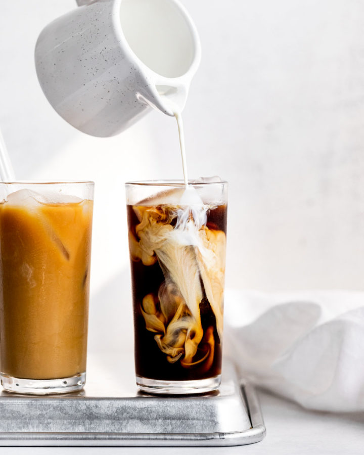 Pouring cream into glass of cold brew next to another glass.
