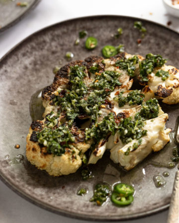 Side view of grilled cauliflower steak with chimichurri sauce on top.