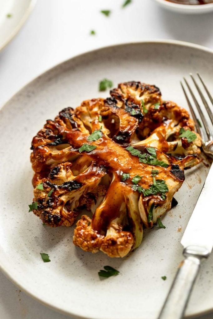 Cauliflower steak on a plate with a knife.