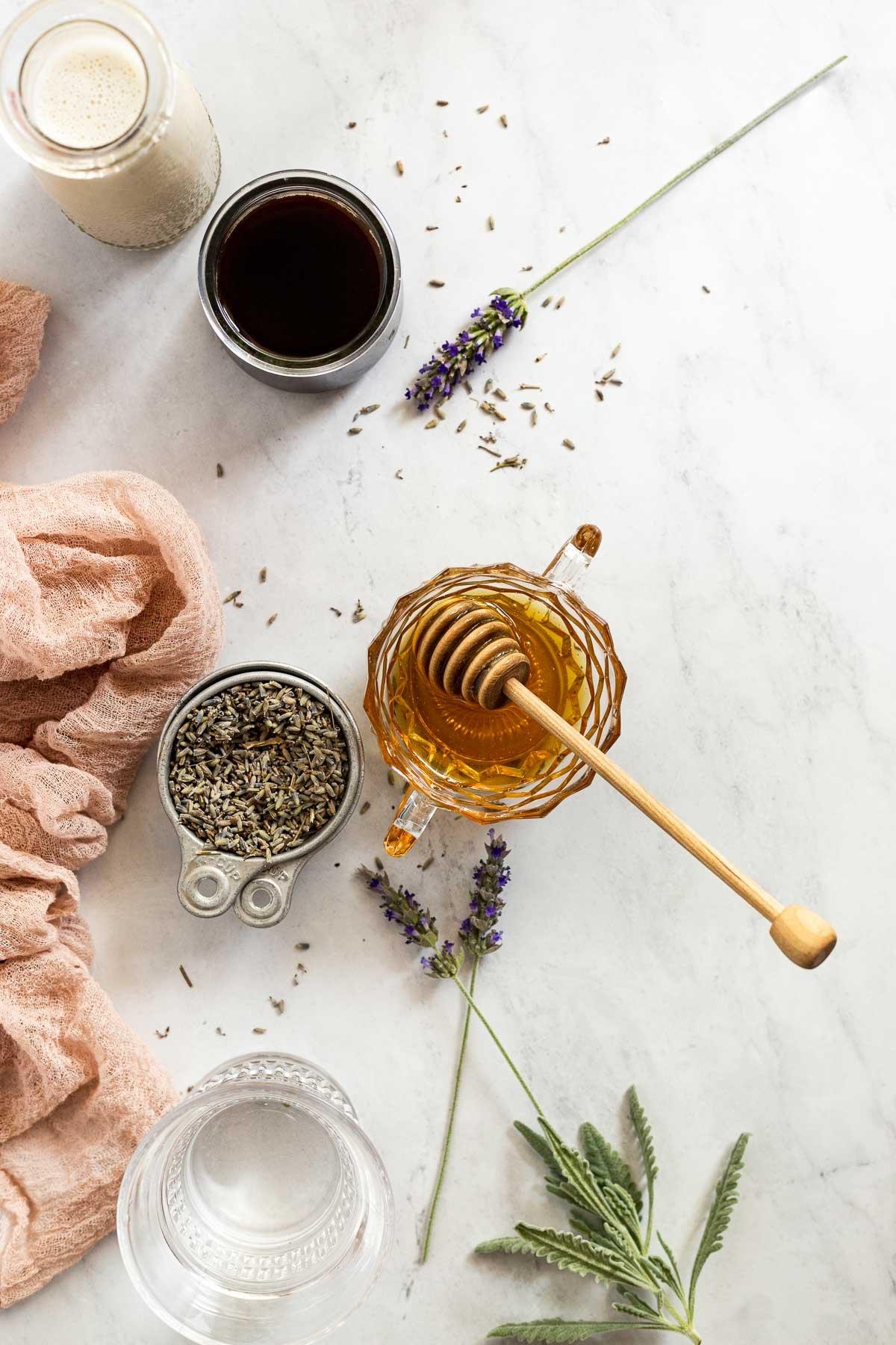 Jar of honey next to lavender, espresso, and oat milk.