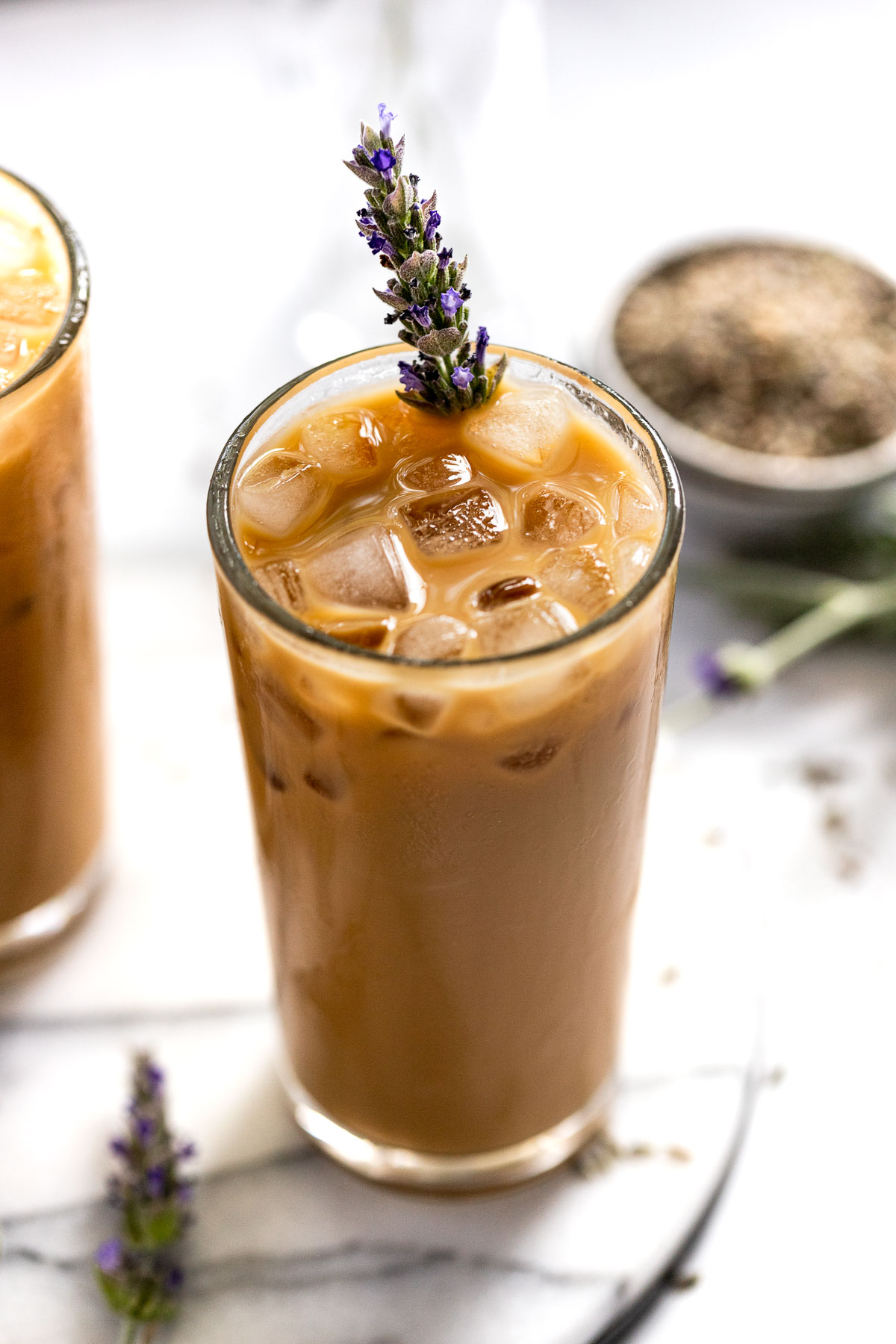 Iced Lavender Latte with lavender sprig on white tray.