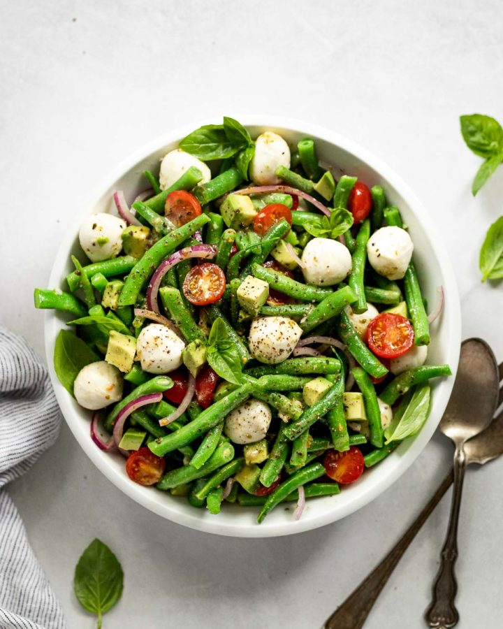 White bowl with green bean salad and mozzarella balls next to spoon and fork.