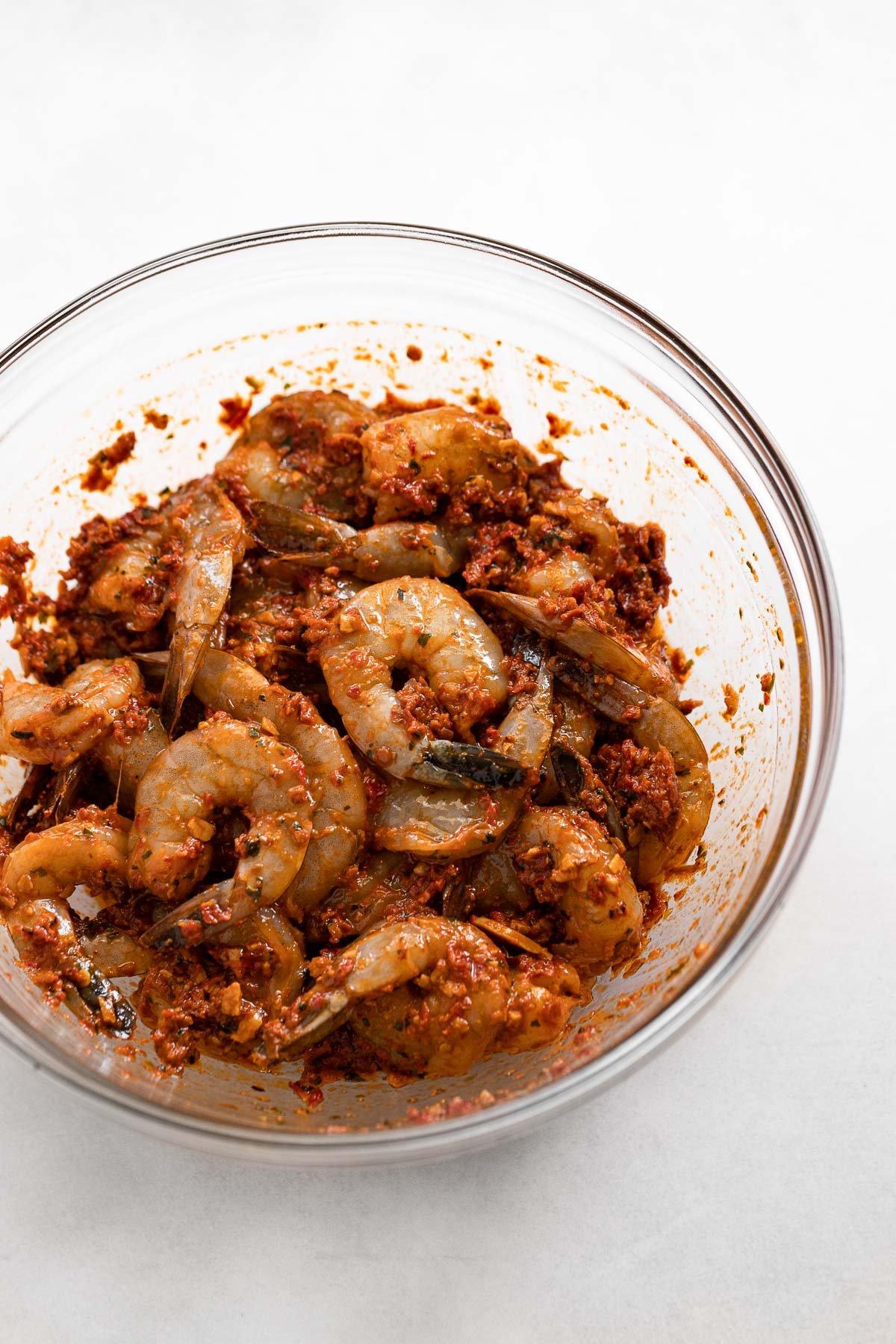 Glass bowl of shrimp tossed in romesco marinade.