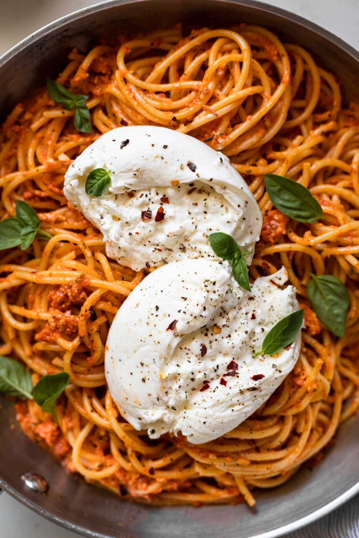 Burrata on top of pasta in a skillet.