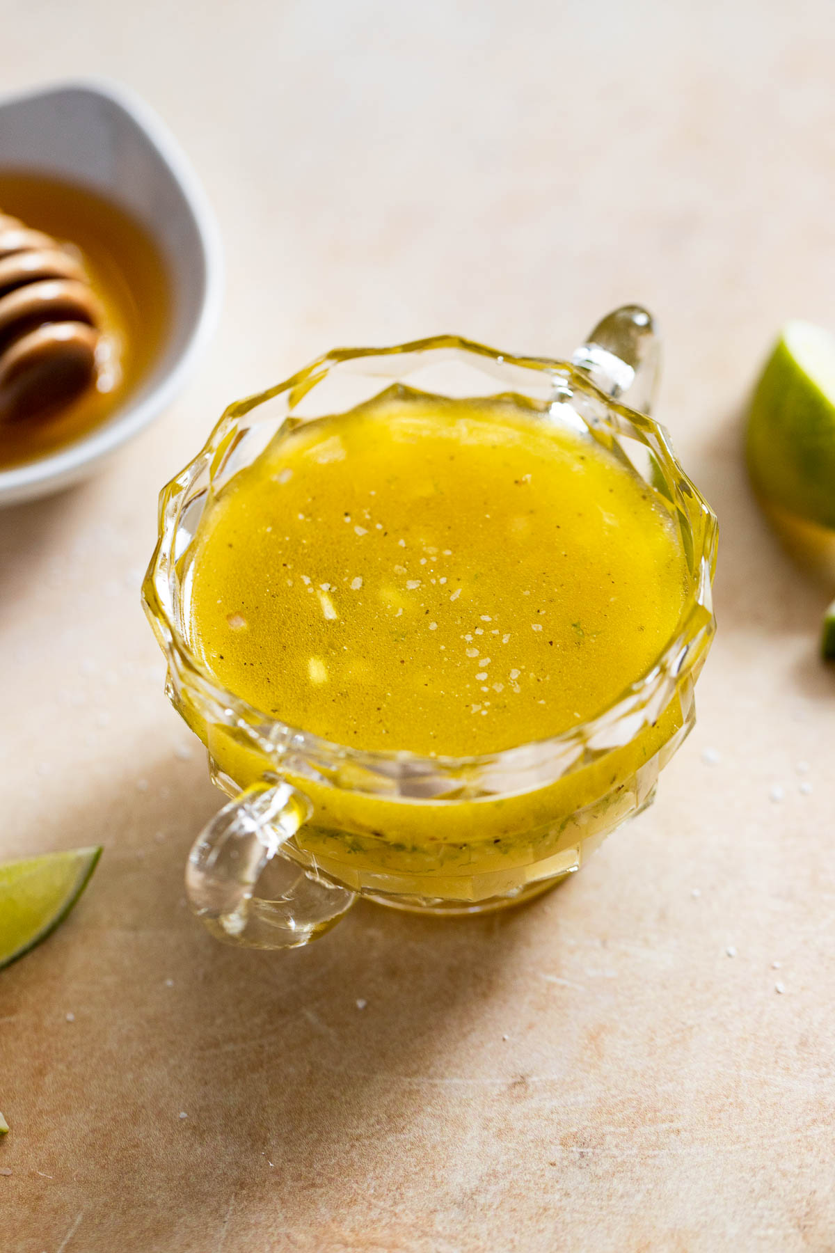 Dressing in glass jar next to limes and honey.
