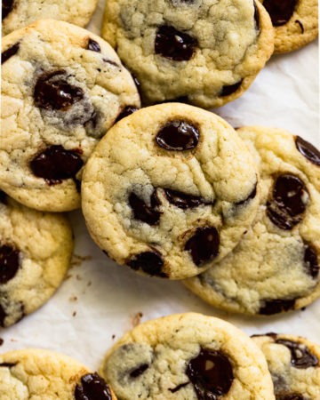 Pile of chocolate chip cookies on parchment paper.