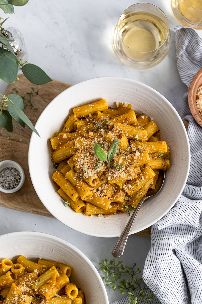 Two pasta bowls with vegan pumpkin sauce pasta and fork.