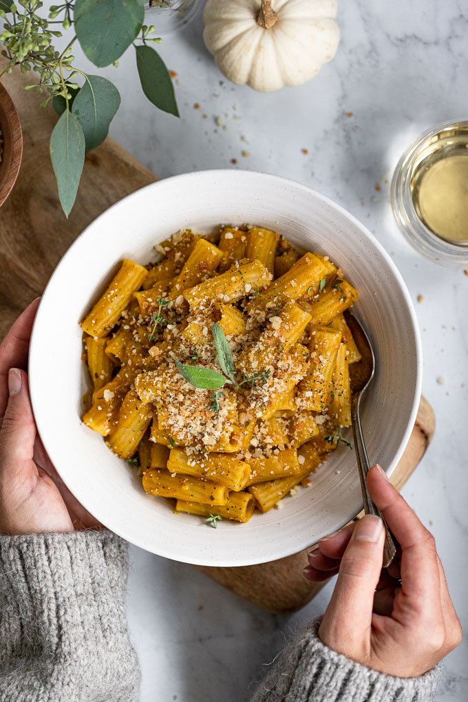 White bowl of pumpkin pasta with hand holding spoon.