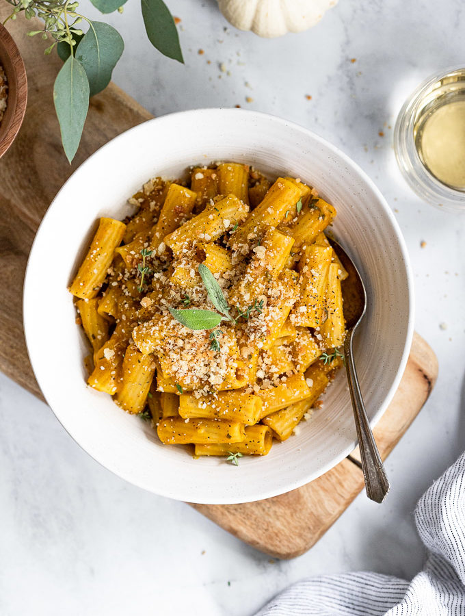 Bowl of rigatoni pasta with fork next to pumpkin and wine.