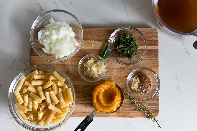 Rigatoni, onion, pumpkin, garlic, herbs, and spices in bowls on cutting board.